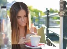 Dziewczyna z telefonem przy kawie, otwierająca konto bankowe.